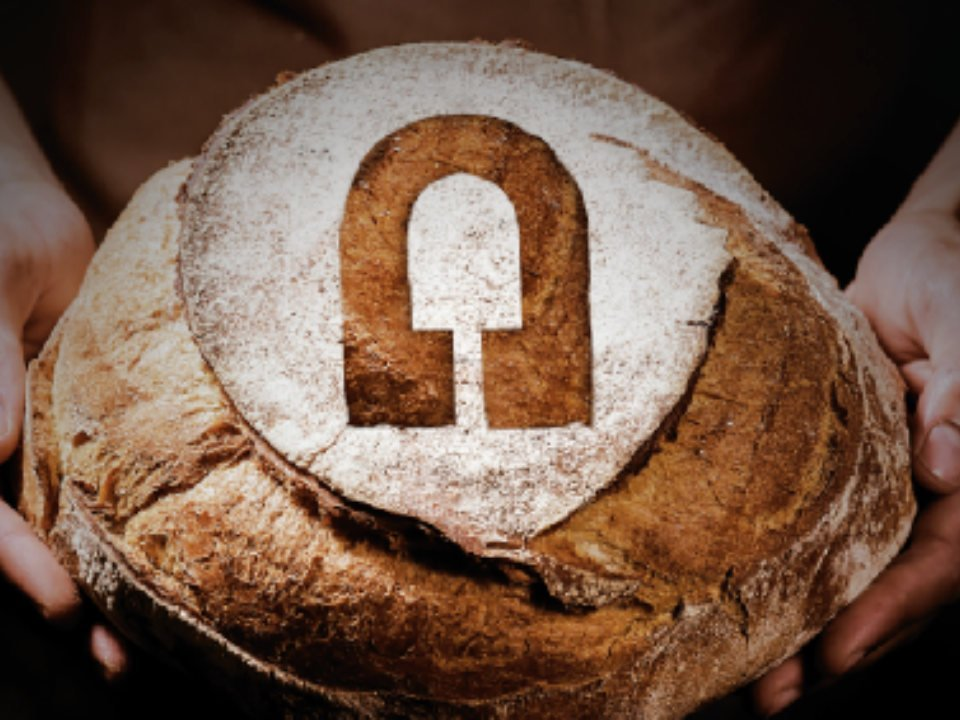 artisan bakeries 2 hands holding a beautiful loaf of round bread with the logo of the bakery a chacun son pain boulangerie a chacun son pain galeries quebec quebec canada ulocal local products local purchase local produce locavore tourist