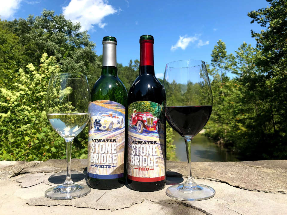 vineyards 2 bottles and glasses of red and white wine from the vineyard on a rock in a natural setting trees and river atwater estate vineyards burdett new york united states ulocal local products local purchase local produce locavore tourist