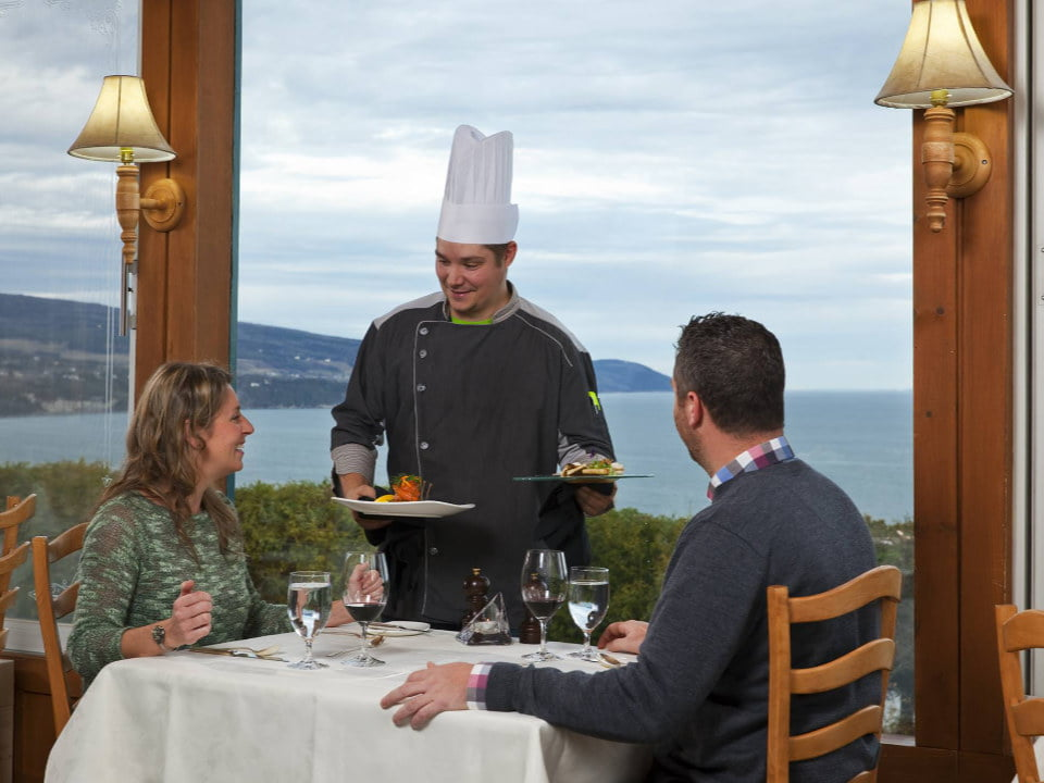 restaurant the chef presents the plates to a couple sitting at a table on the edge of the window with a magnificent view of la malbaie auberge des 3 canards la malbaie quebec canada ulocal local products local purchase local produce locavore tourist