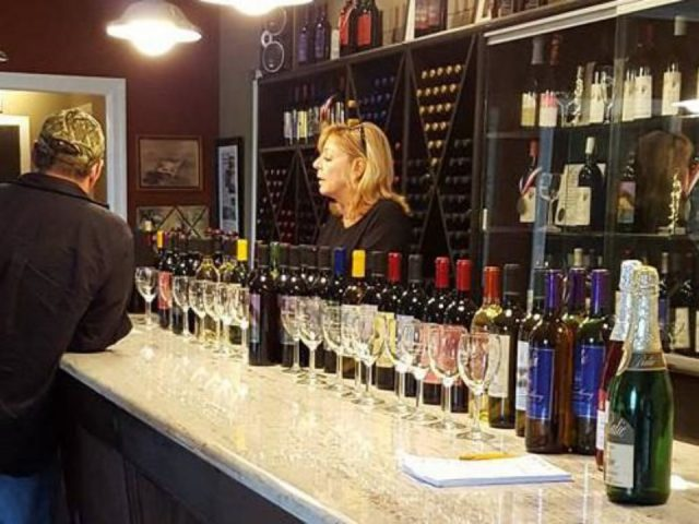 vignoble client au bar de dégustation avec employée avec présentoir de tous les vins balic winery mays landing new jersey états unis ulocal produits locaux achat local produits du terroir locavore touriste