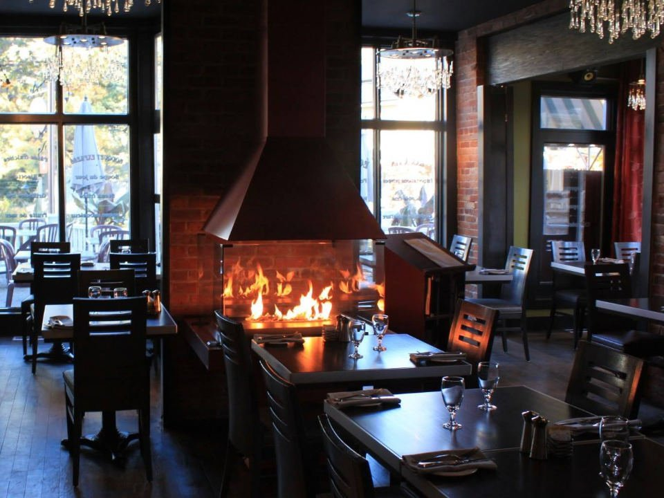 restaurant bistro interior relaxed atmosphere with fireplace in the center of the tables with large windows bistro la muse baie-saint-paul quebec canada ulocal local products local purchase local produce locavore tourist