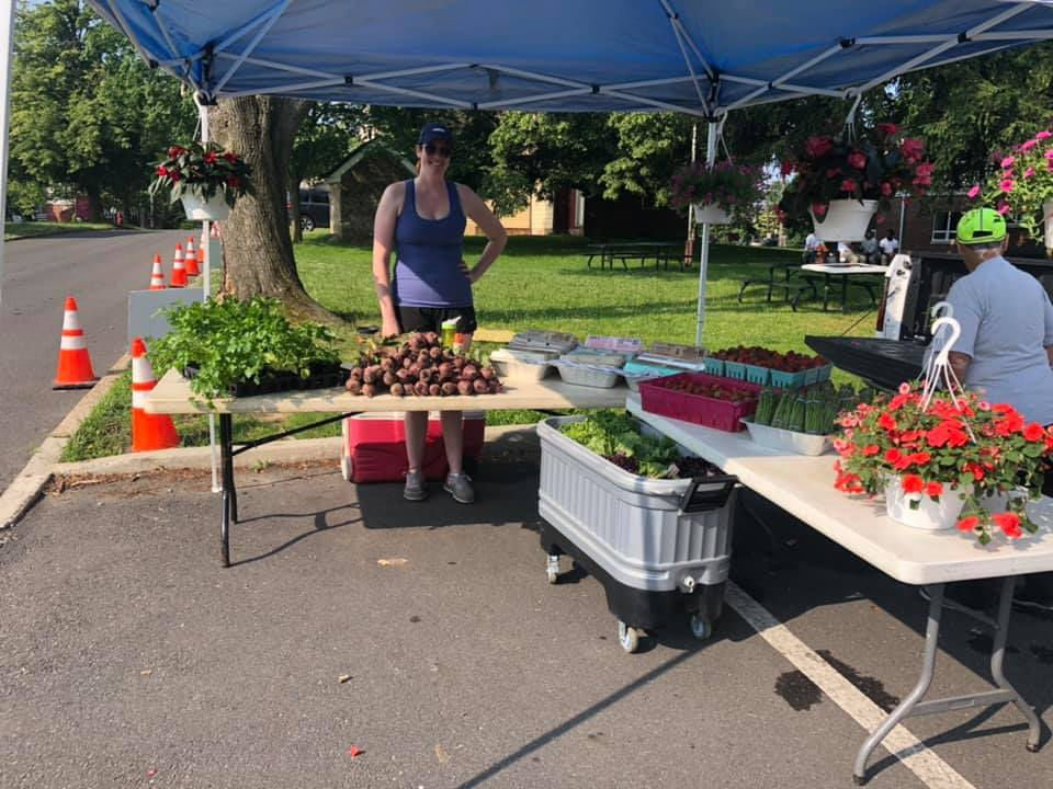 public markets kiosk of flowers and vegetables with a happy representative bordentown farmers market bordentown new jersey united states ulocal local products local purchase local produce locavore tourist