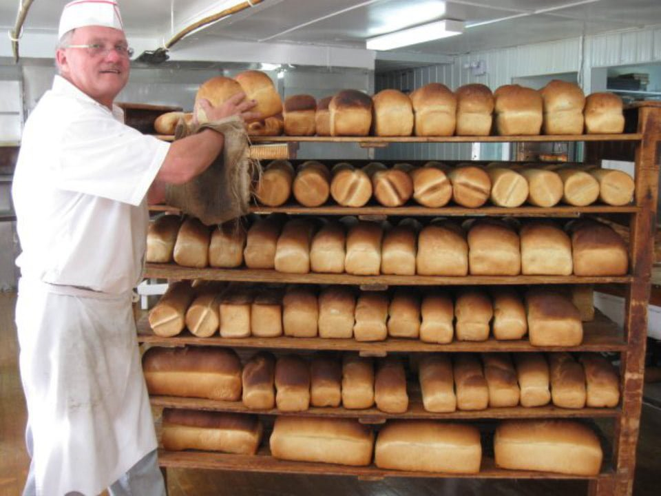 artisan bakeries baker putting his loaves in the shelf boulangerie bouchard isle-aux-coudres quebec canada ulocal local products local purchase local produce locavore tourist