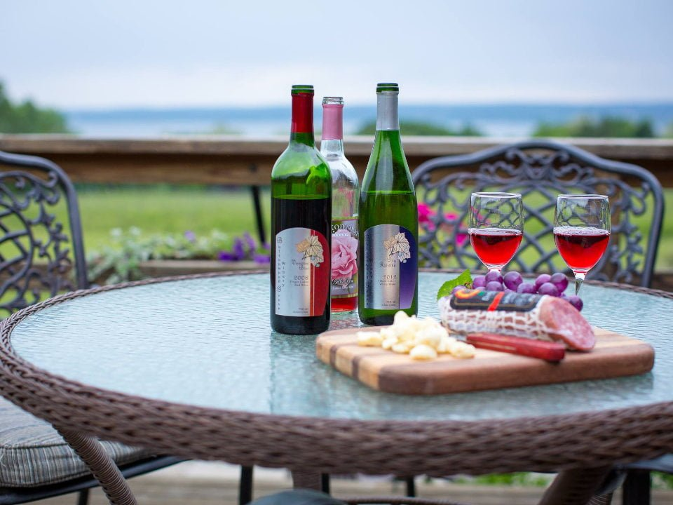 vineyards 3 bottles and 2 glasses of wine on a terrace table with cheese platter and cold cuts buttonwood grove winery ovid new york united states ulocal local products local purchase local produce locavore tourist