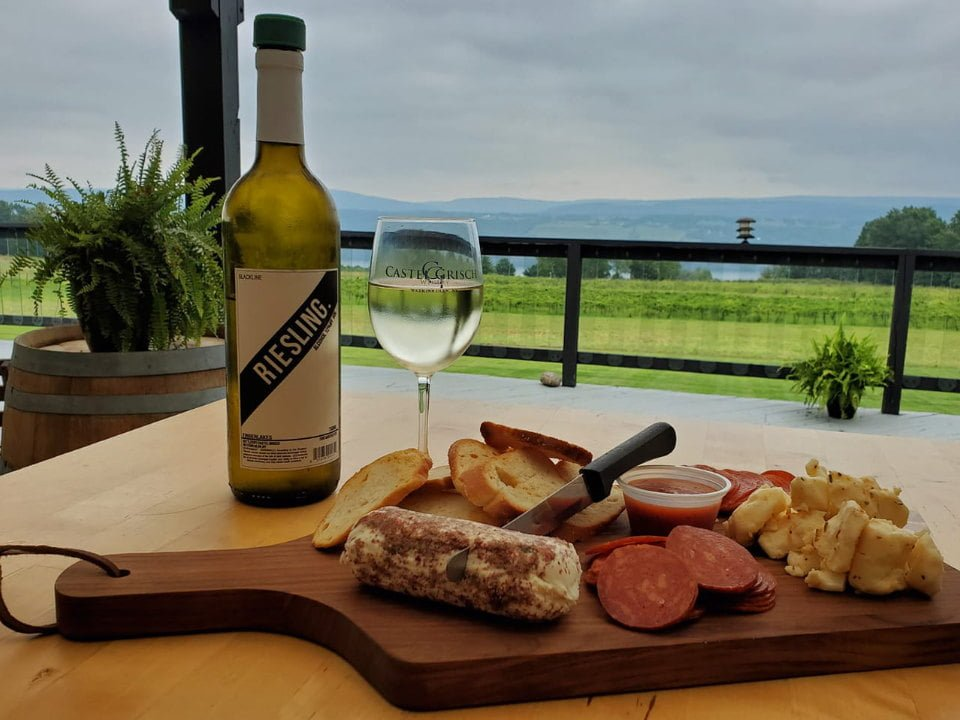 vineyards bottle and glass of white wine with platter of cheese snacks and bread on a table on the terrace overlooking the seneca lake castle grisch winery watkins glen new york united states ulocal local products local purchase local produce locavore tourist