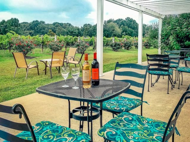 vineyard tables with 2 bottles and glasses of wine and chairs on the beautiful patio terrace overlooking the vineyard coda rossa winery franklinville new jersey united states ulocal local products local purchase local produce locavore tourist