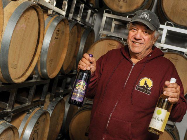 vignoble philip randazzo propriétaire dans sa cave entouré de tonneaux de cèdre qui tient deux bouteilles de vin et à gauche avec la nouvelle étiquette de vin coyote moon vineyards clayton new york états unis ulocal produits locaux achat local produits du terroir locavore touriste