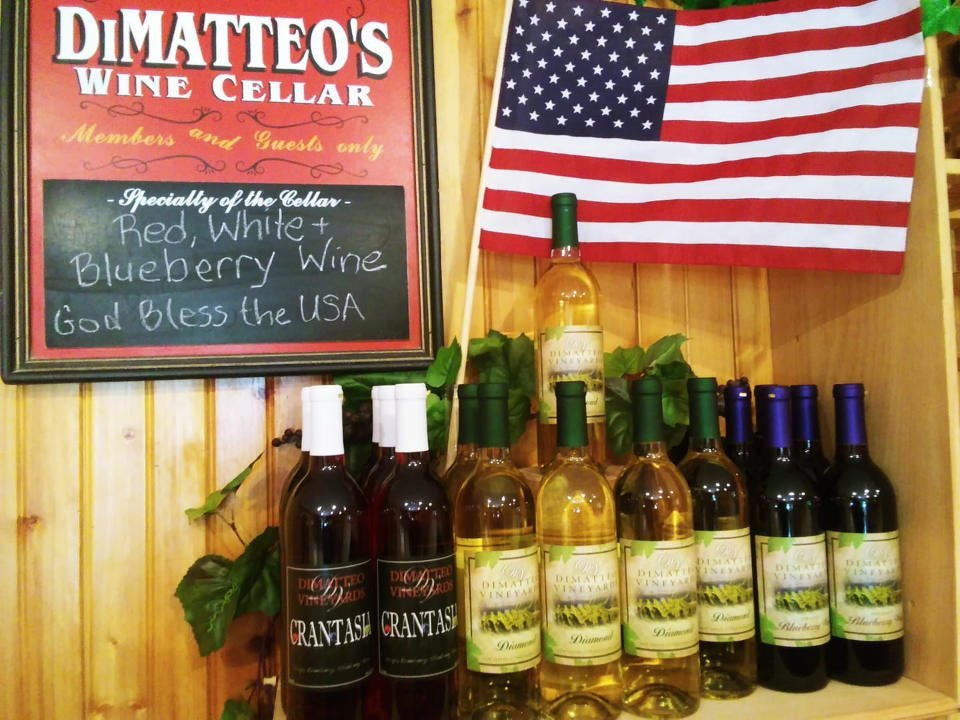 vineyard red, white and blueberry bottles on table with united states flag and chalkboard dimatteo vineyards hammonton new jersey united states ulocal local products local purchase local produce locavore tourist