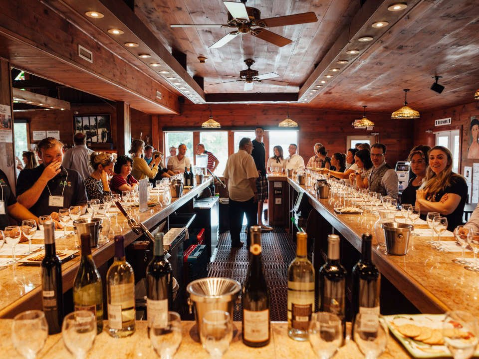 vineyards tasting room with wood paneling and large central bar with customers around duck walk vineyards hamptons water mill new york united states ulocal local products local purchase local produce locavore tourist
