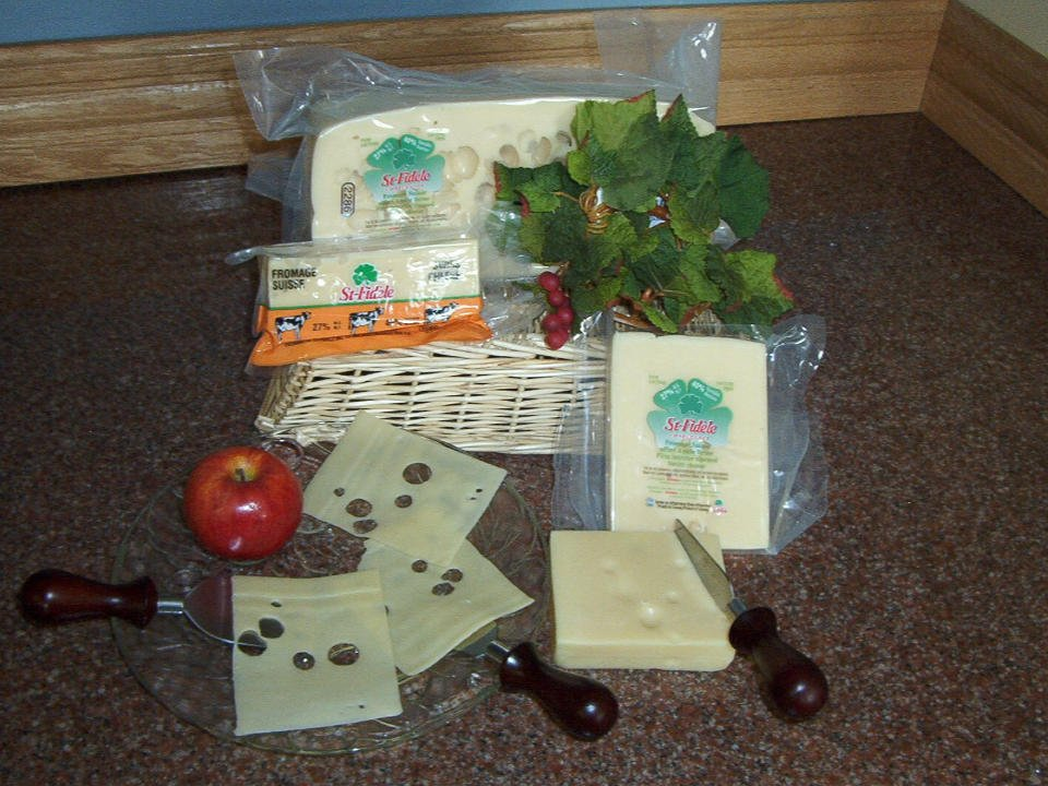 cheese factories basket with cheese brick swiss platter with red apple and swiss cheese and cheddar cheese brick with knives on the table fromagerie st-fidèle la malbaie quebec canada ulocal local products local purchase local produce locavore tourist