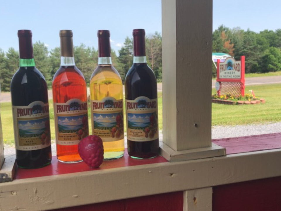 vineyards 4 bottles of diversified fruit wine with the vineyard sign in the background fruit yard winery dundee new york united states ulocal local products local purchase local produce locavore tourist