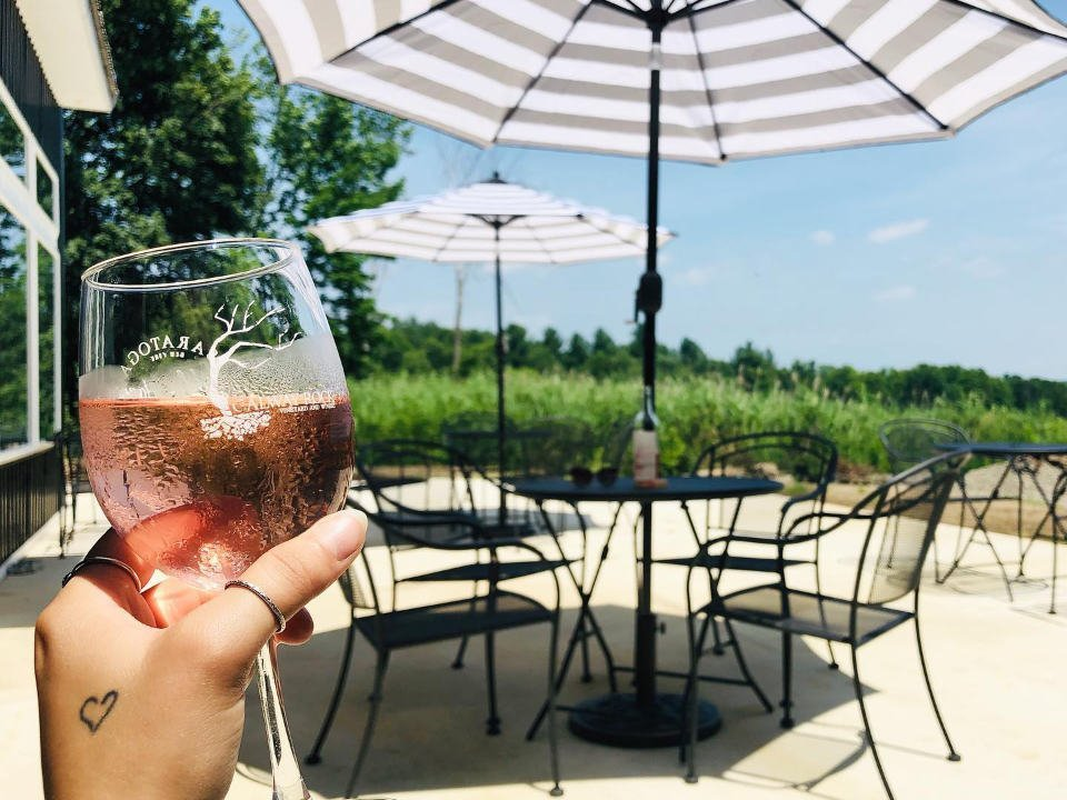 vignoble verre de vin rosé avec vue du patio avec chaises tables et parasols galway rock vineyard and winery ballston lake new york états unis ulocal produits locaux achat local produits du terroir locavore touriste
