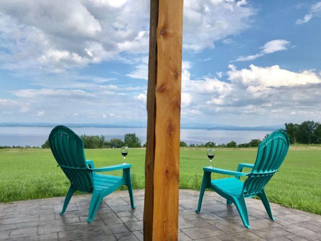 vineyards 2 green chairs and glass of red wine with a pole in the center and view of the estate and lake champlain highlands vineyard keeseville new york united states ulocal local products local purchase local produce locavore tourist