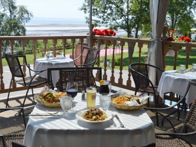 restaurant table prepared with 3 plates local ingredients on the terrace with stunning views of the shore hôtel cap-aux-pierres la baleine quebec canada ulocal local products local purchase local produce locavore tourist