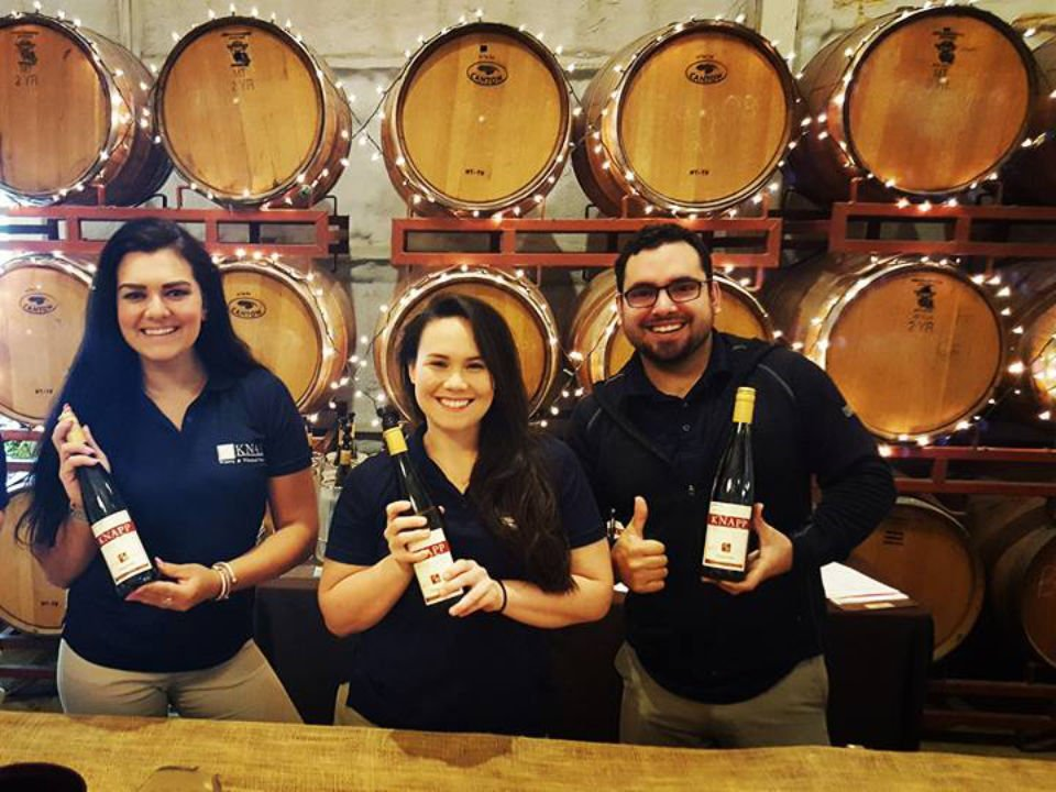 vineyards 3 smiling employees with a bottle of wine in their hands with cedar barrels in the background knapp winery romulus new york united states ulocal local products local purchase local produce locavore tourist