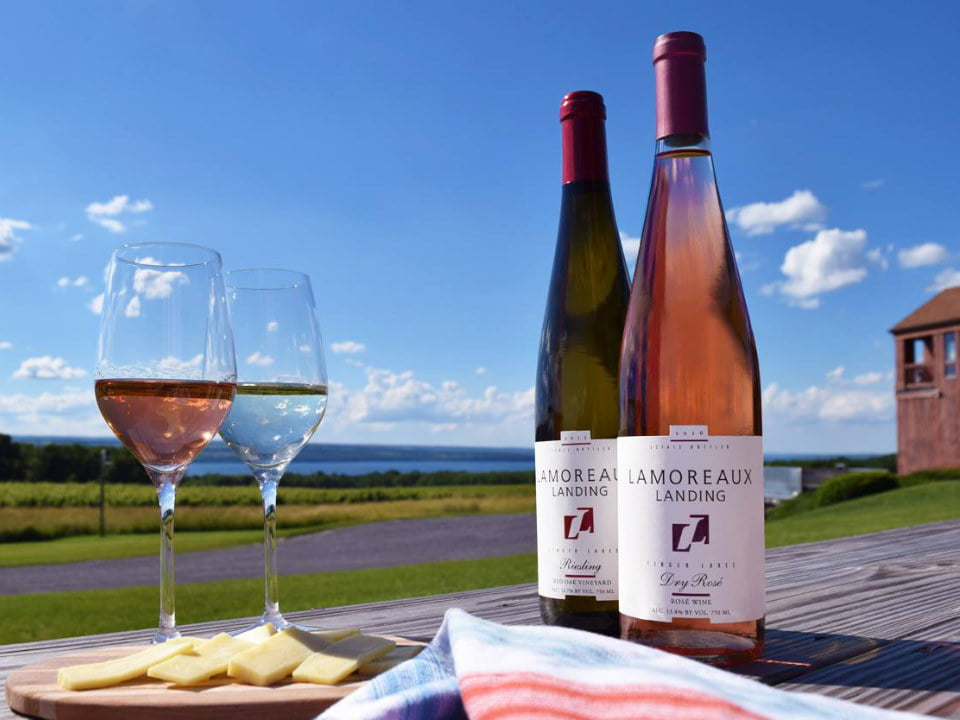 vineyards 2 bottles and 2 glasses of white and rosé wine on a table with the view of the estate and the winery with a beautiful sun lamoreaux landing wine cellars lodi new york united states ulocal local products local purchase local produce locavore tourist