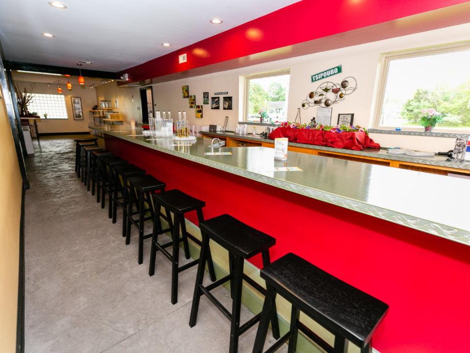 alcool grand bar avec banc dans la salle de dégustation avec un accent de rouge lazy eye distillery richland new jersey united states ulocal produits locaux achat local produits du terroir locavore touriste