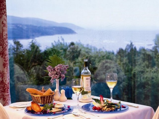 restaurant table prepared with 2 plates local ingredients with bottle and 2 glass of white wine with breathtaking views of the river le perché gourmand la malbaie quebec canada ulocal local products local purchase local produce locavore tourist