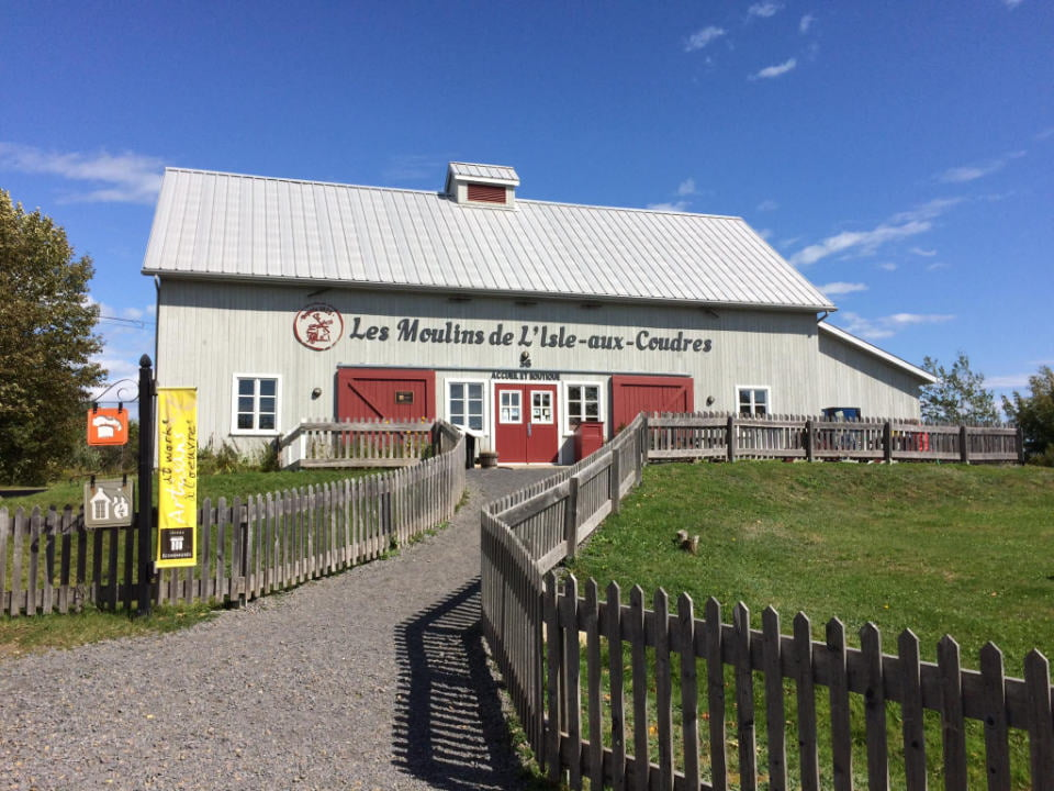 food stores shop and reception desk of the exterior building in gray wood with red doors les moulins de l'isle-aux-coudres l'isle-aux-coudres quebec canada ulocal local products local purchase local produce locavore tourist