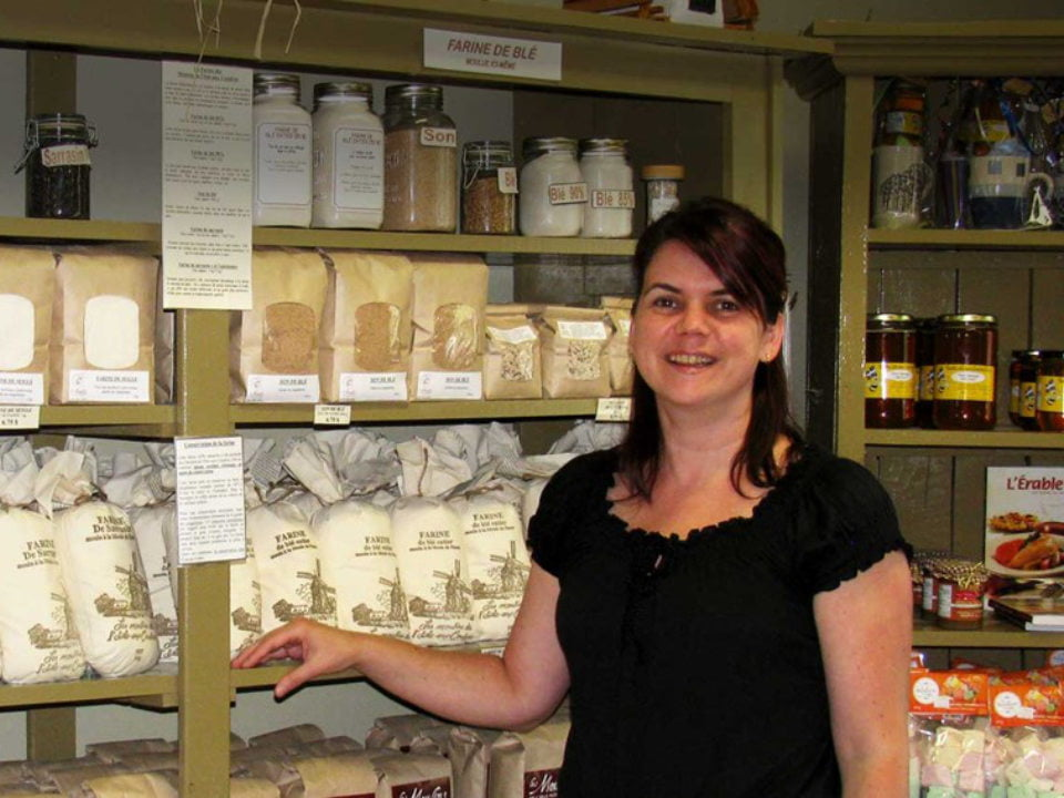 food stores indoor shop with employee next to a shelf filled with ground flour sacks and other homemade products les moulins de l'isle-aux-coudres l'isle-aux-coudres quebec canada ulocal local products local purchase local produce locavore tourist