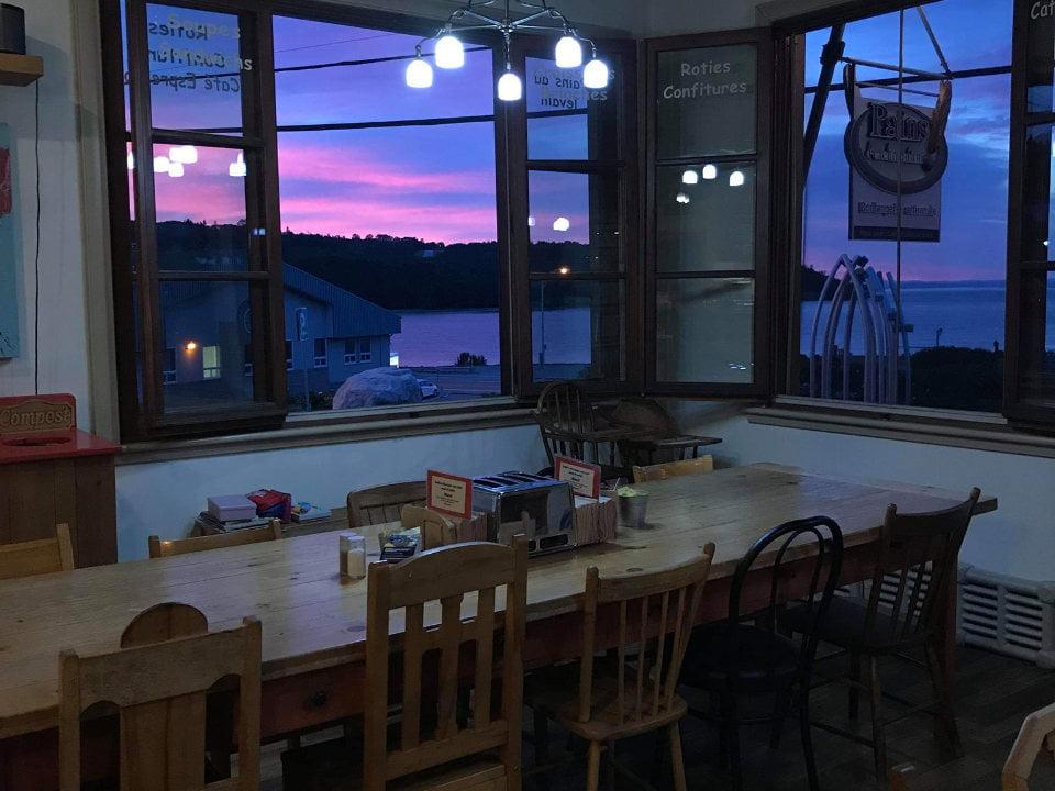 boulangerie artisanale longue table en bois près de la fenêtre avec magnifique vue nocturne de la baie pains d'exclamation la malbaie quebec canada ulocal produits locaux achat local produits du terroir locavore touriste