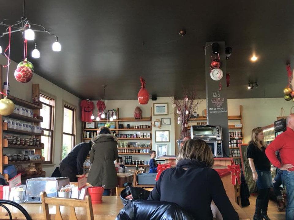 boulangerie artisanale intérieur de la boulangerie avec clients aux comptoir de commande et d'autres assis aux tables pains d'exclamation la malbaie quebec canada ulocal produits locaux achat local produits du terroir locavore touriste