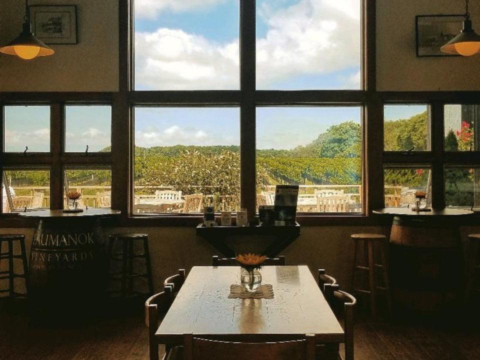 vignoble salle de dégustation avec table en bois et vue de la terrasse par la fenêtre paumanok vineyards aquebogue new york états unis ulocal produits locaux achat local produits du terroir locavore touriste