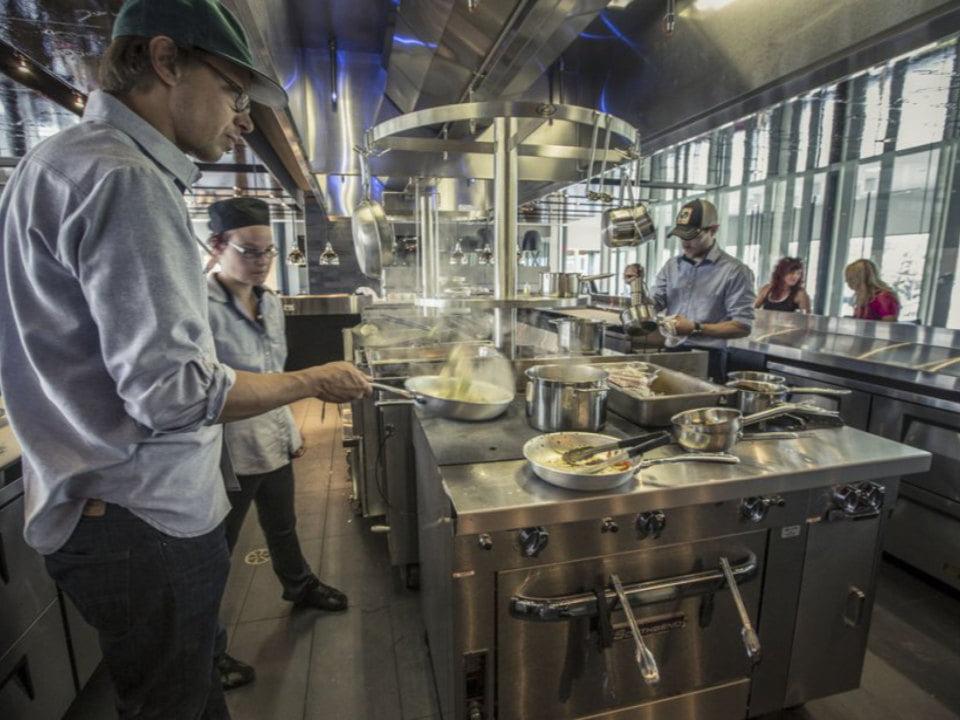 restaurant cuisine commerciale moderne avec chefs qui préparent des assiettes restaurant les labours baie-saint-paul quebec canada ulocal produits locaux achat local produits du terroir locavore touriste