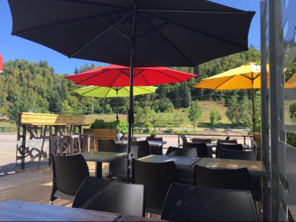 restaurant nice terrace with umbrellas of different colors red yellow green black with nature view resto-pub belles et bum la malbaie quebec canada ulocal local products local purchase local produce locavore tourist