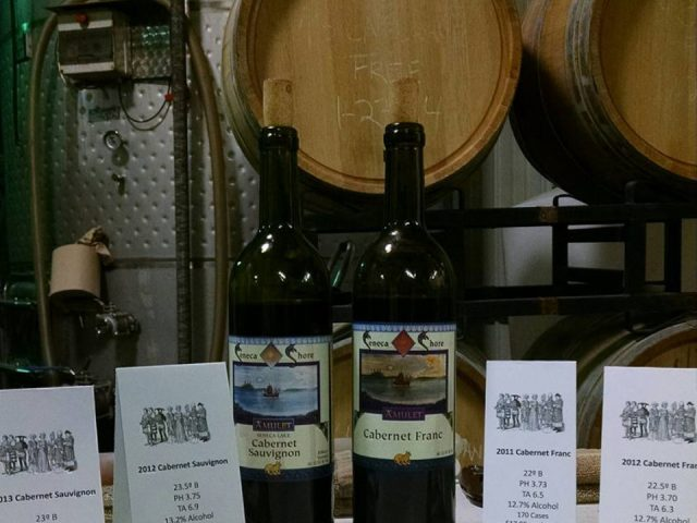 vineyards 2 bottles of red wine in the cellar with wooden barrels in the background seneca shore wine cellars penn yan new york united states ulocal local products local purchase local produce locavore tourist