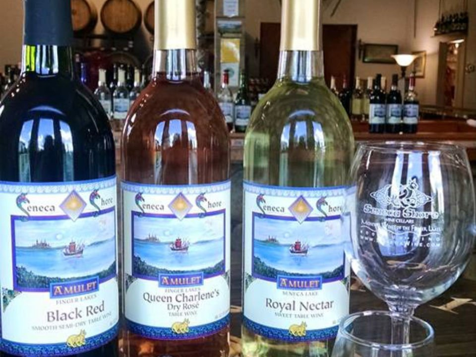 vineyards 3 bottles of red rosé and white wine with glass and bowl of grapes and medieval decor in the background seneca shore wine cellars penn yan new york united states ulocal local products local purchase local produce locavore tourist