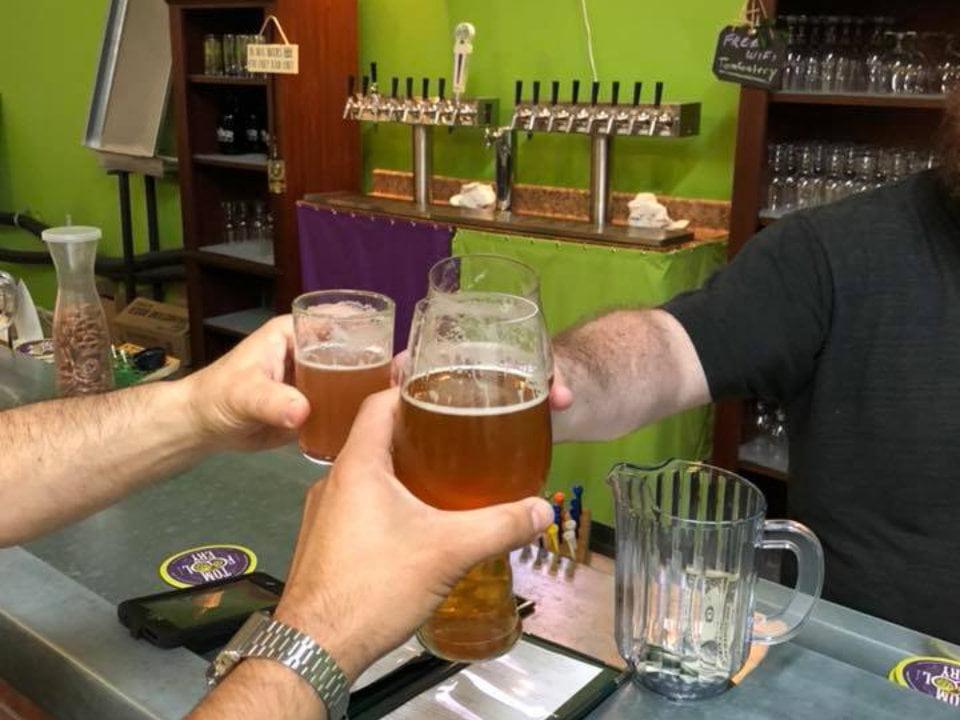 microbrasseries mains qui lèvent leur verres de bière artisanale au bar de dégustation tomfoolery brewing hammonton new jersey états unis ulocal produits locaux achat local produits du terroir locavore touriste