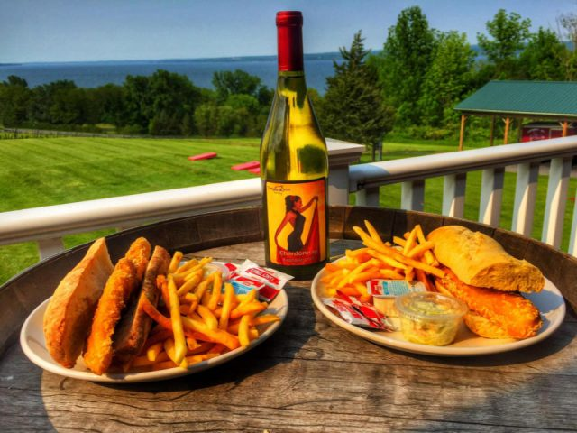 vineyards 2 plates of fish sandwich with fries and bottle of wine on a patio table with magnificent view of the estate and the lake toro run winery ovid new york united states ulocal local products local purchase local produce locavore tourist