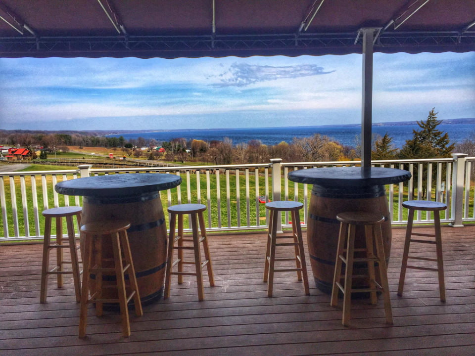 vineyards covered terrace with tables made with barrels and wooden benches and unobstructed view of the land and lake toro run winery ovid new york united states ulocal local products local purchase local produce locavore tourist