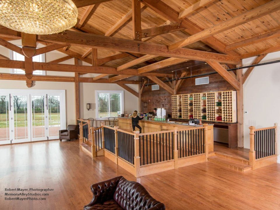 vineyard beautiful tasting room with wood paneling with a customer and an employee at the bar and brown couches willow creek farm and winery west cape may new jersey united states ulocal local products local purchase local produce locavore tourist
