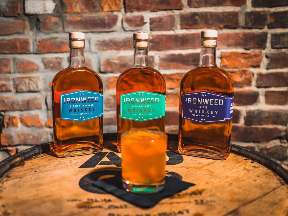 alcool 3 bouteilles de spiritueux sur un tonneau de bois avec un verre albany distilling co albany new york états unis ulocal produits locaux achat local produits du terroir locavore touriste
