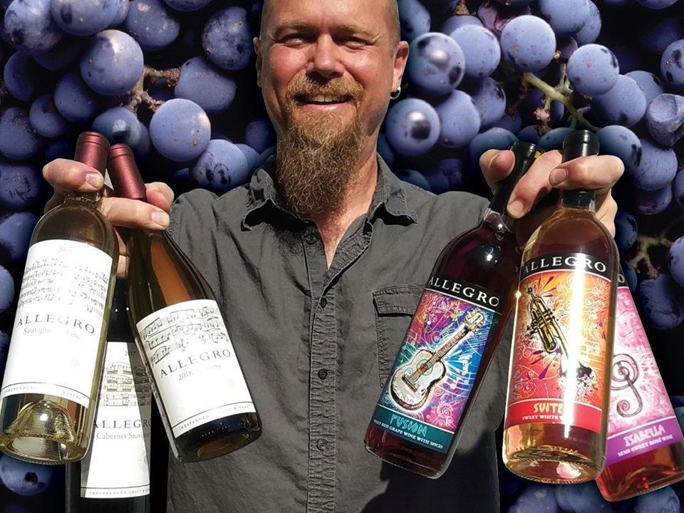 vignoble propriétaire avec 3 bouteilles de vin dans chaque main et raisin en arrière plan allegro vineyards and winery brogue pennsylvanie états unis ulocal produits locaux achat local produits du terroir locavore touriste