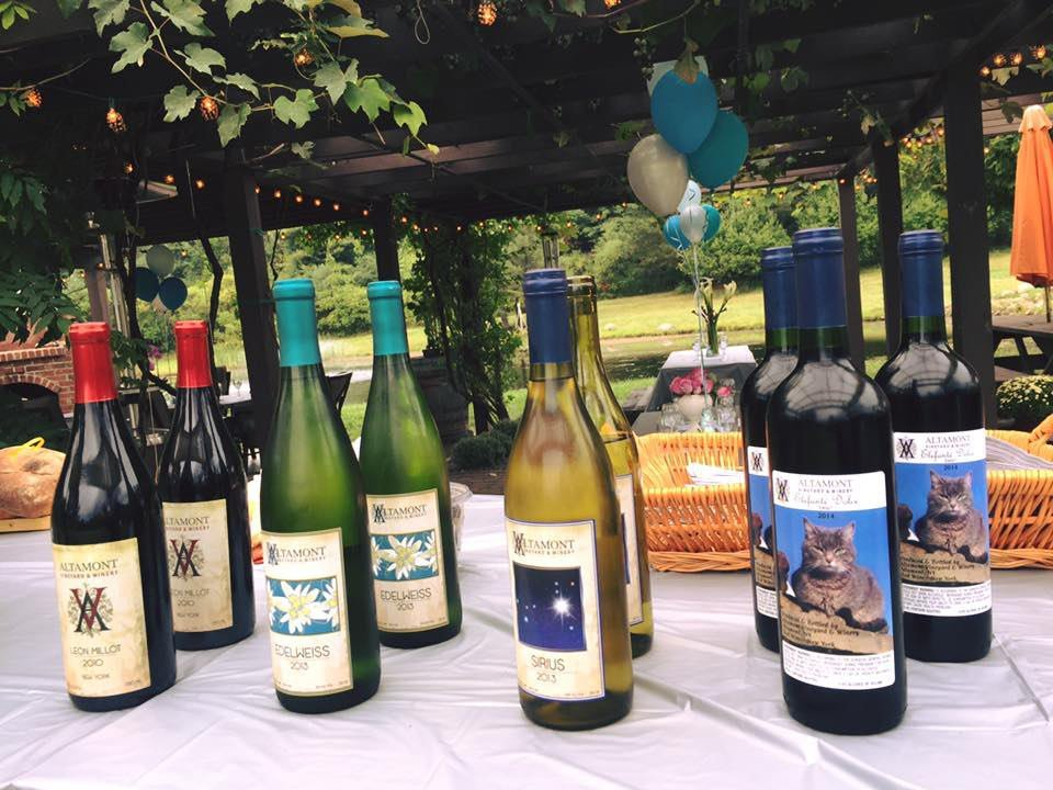 vineyards assortment of wine bottles from vineyard on a table outside with covered terrace in the background altamont vineyard and winery altamont new york united states ulocal local products local purchase local produce locavore tourist