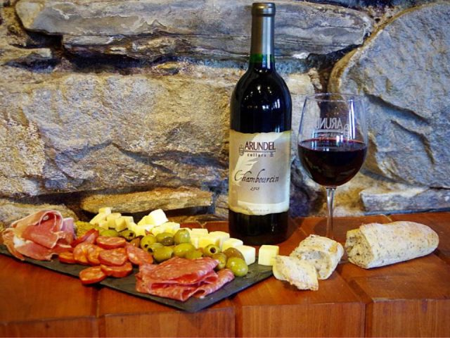 vineyards bottle and glass of red wine on a stone wall shelf with cheese plate bread and cold cuts arundel cellars and brewing co north east pennsylvania united states ulocal local products local purchase local produce locavore tourist