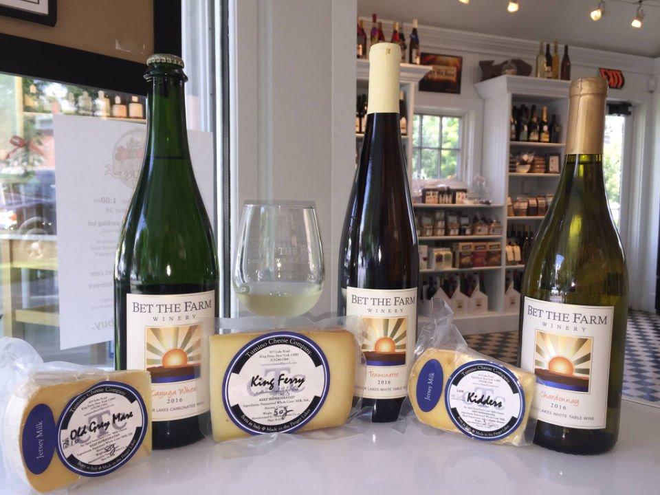 vineyards 3 bottles and glasses of wine from the vineyard matched with local cheeses on a table in the boutique bet the farm winery trumansburg new york united states ulocal local products local purchase local produce locavore tourist