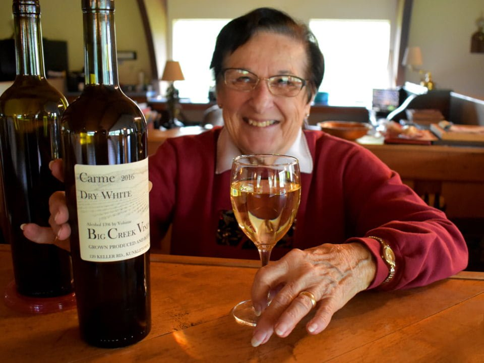 vineyards grandma millie with a glass of white wine and 2 bottles of the vineyard at the tasting bar big creek vineyard kunkletown pennsylvania united states ulocal local products local purchase local produce locavore tourist