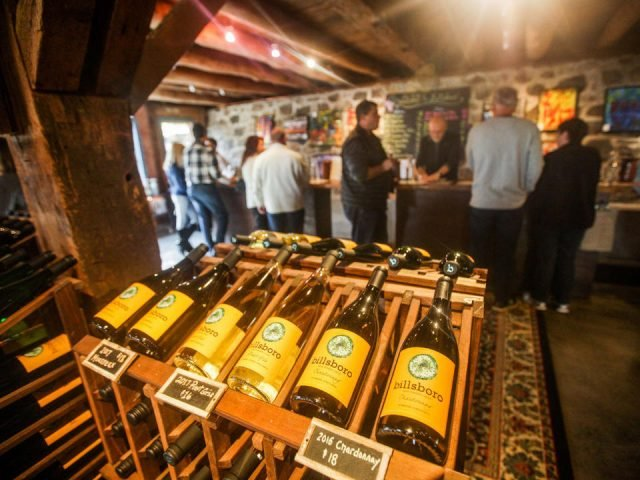 vineyards tasting room with people at the bar and display of wine bottles in front billsboro winery geneva new york united states ulocal local products local purchase local produce locavore tourist