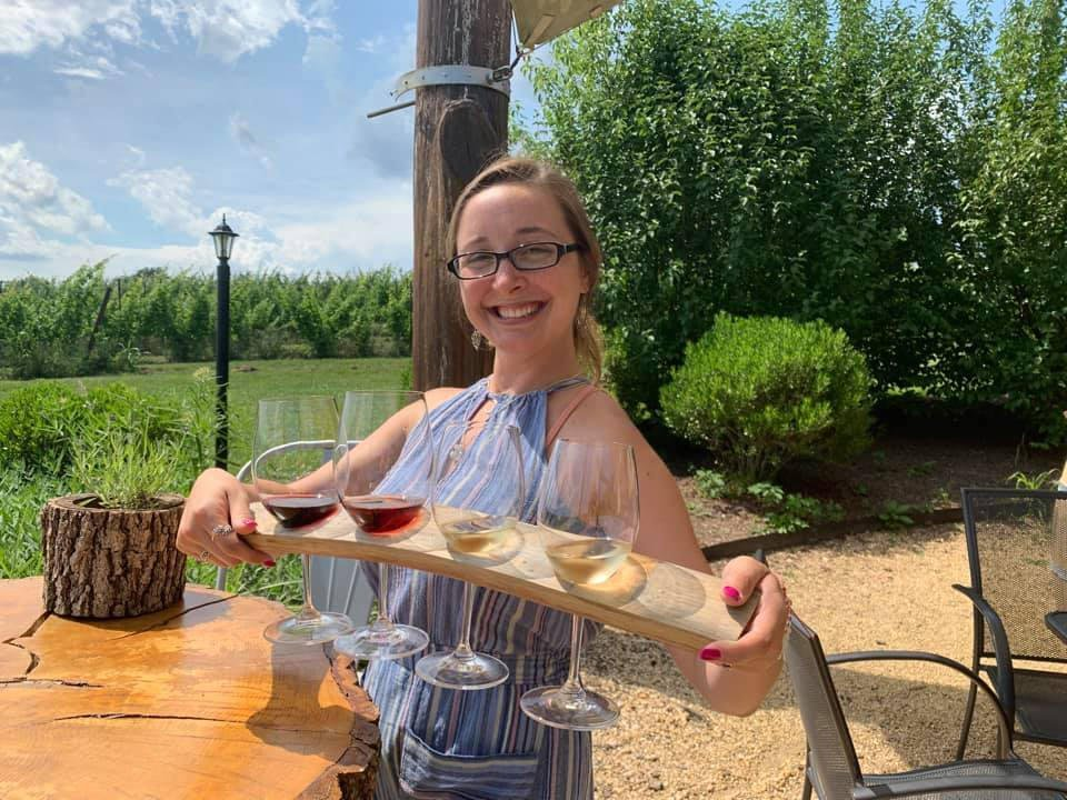 vineyards smiling employee with a tasting tray of glasses of wine on the terrace black ankle vineyards mount airy maryland united states ulocal local products local purchase local produce locavore tourist