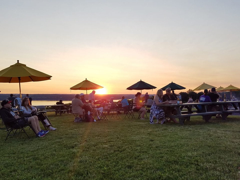 vineyards large lot on the lakeside with picnic tables and umbrellas with people enjoying the good wine and the sunset boundary breaks vineyard lodi new york united states ulocal local products local purchase local produce locavore tourist