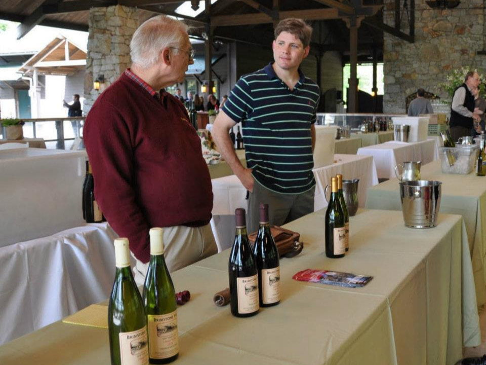 vignoble 2 hommes debout à une table avec bouteilles de vin pour dégustations dans une grande salle et clients brimstone hill vineyard pine bush new york états unis ulocal produits locaux achat local produits du terroir locavore touriste