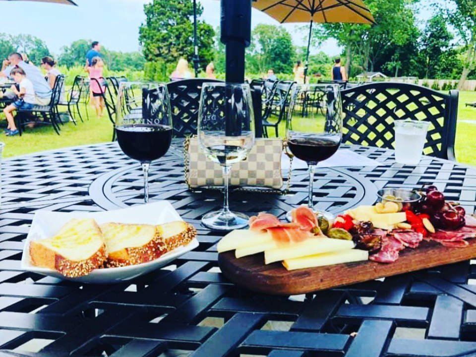 vineyards 3 glasses of wine tasting on a table outside with local side dish and guests enjoying the terrace in the background del vino vineyards northport new york united states ulocal local products local purchase local produce locavore tourist