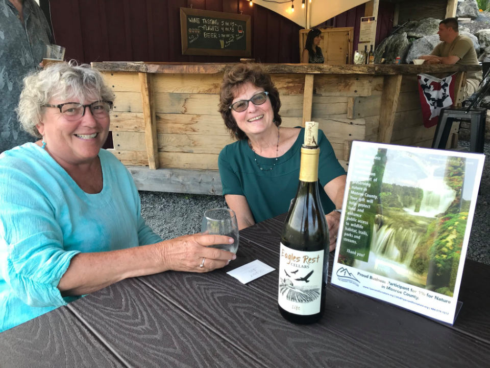 vineyards 2 women enjoying a glass of wine at a table with outdoor tasting bar eagles rest cellars stroudsburg pennsylvania united states ulocal local products local purchase local produce locavore tourist
