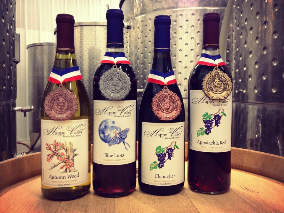 vignoble assortiment de bouteilles de vin primées du vignoble dans la salle de production du vin avec réservoirs en acier inoxydable happy valley vineyard and winery state college pennsylvanie états unis ulocal produits locaux achat local produits du terroir locavore touriste