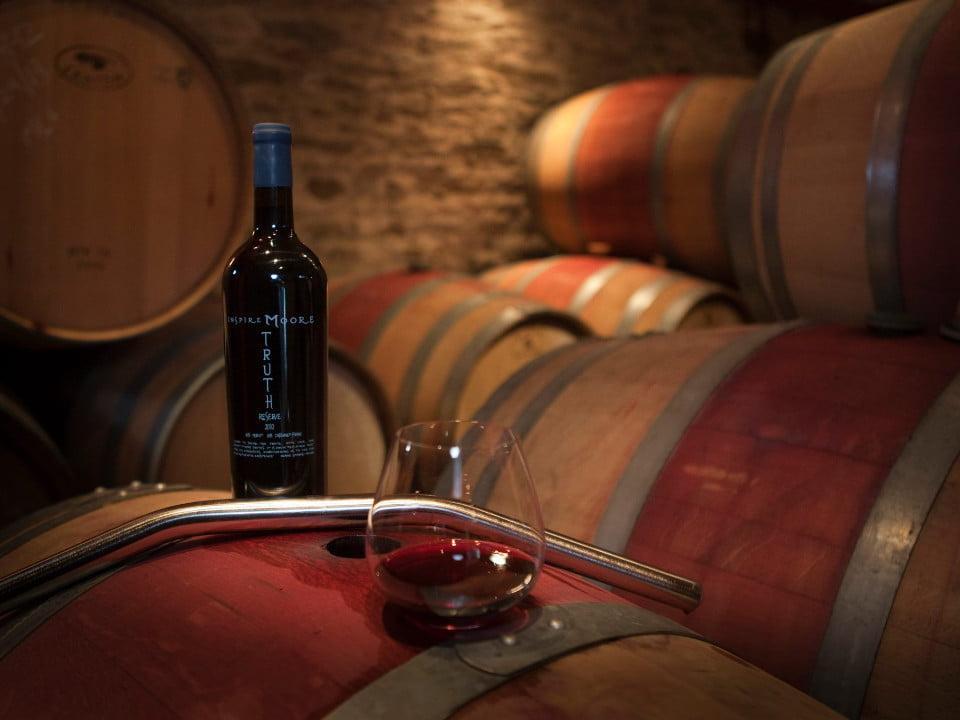 vignoble bouteille et verre de vin rouge dans la cave à vin sur des tonneaux de cèdres inspire moore winery naples new york états unis ulocal produits locaux achat local produits du terroir locavore touriste
