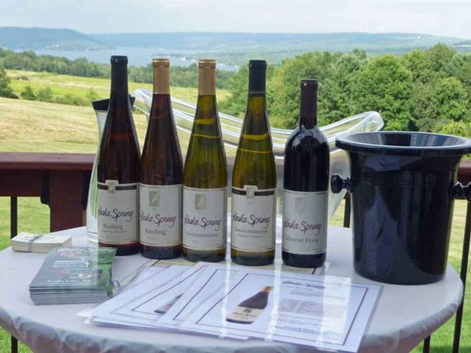 vignoble 5 bouteilles de vin avec ceau sur une table dehors avec vue sur le vignoble et le lac keuka spring vineyards penn yan new york états unis ulocal produits locaux achat local produits du terroir locavore touriste